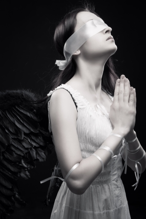 angel alone: Pretty girl with artificial wings praying over dark background Stock Photo