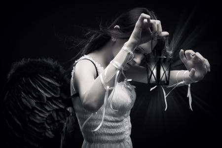 Pretty angel with lantern posing over dark background