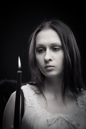 Pretty girl with candle over dark background photo