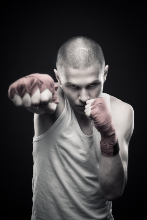 Young agressive boxer posing over dark background Stock Photo - 13622994
