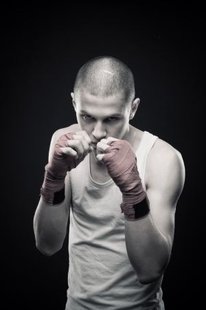 Young aggressive boxer posing over dark background Stock Photo - 13646284