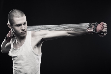 Young sportsmen stretching expander over dark background Stock Photo - 13646283