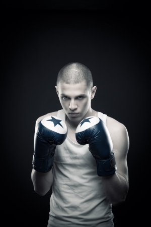 Young aggressive boxer posing over dark background Stock Photo - 13661664