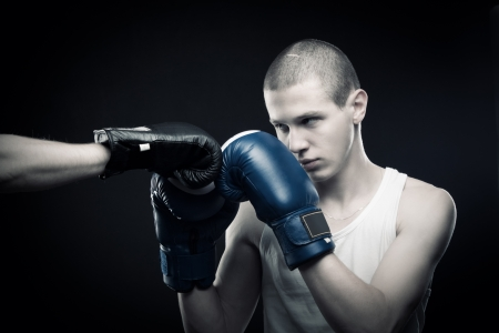 dauntless: Boxer fighting with another one over dark background Stock Photo
