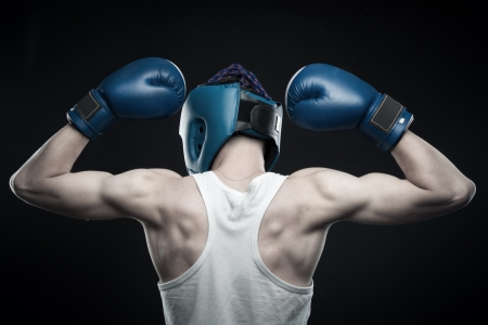dauntless: Strong boxer in gloves posing over dark background. Rear view.