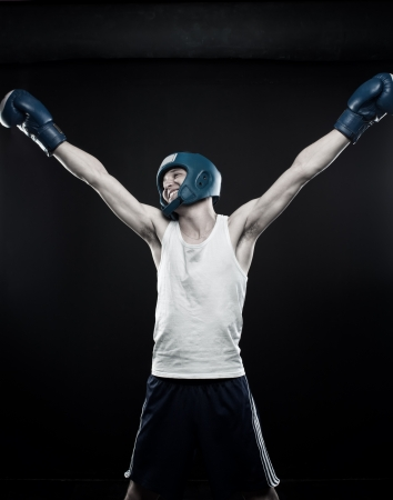 dauntless: Young boxer posing over dark background Stock Photo