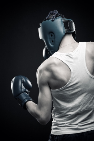 dauntless: Rear view of young boxer. Over dark background. Stock Photo