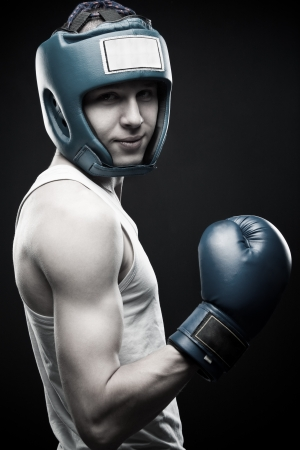 Young boxer posing over dark background Stock Photo - 13793900