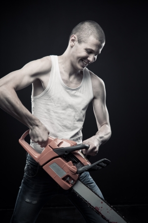 Angry man with bloody chainsaw posing over dark background photo