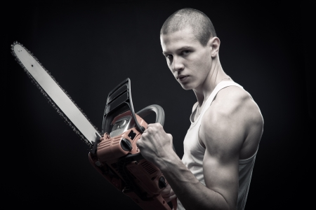 Young strong guy with chainsaw posing over dark background photo