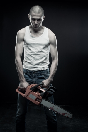 nightmare: Young strong guy with chainsaw posing over dark background Stock Photo