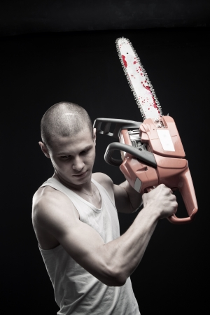 Young strong guy with bloody chainsaw posing over dark background photo