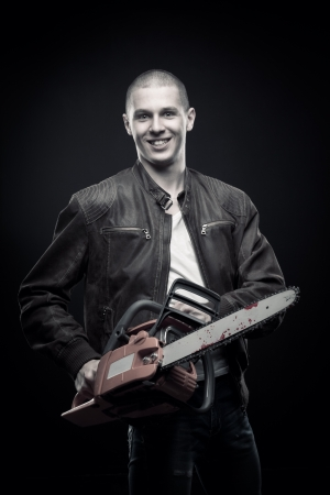Mad guy with bloody chainsaw posing over dark background photo