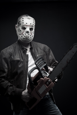 guy in mask with bloody chainsaw posing over dark background photo