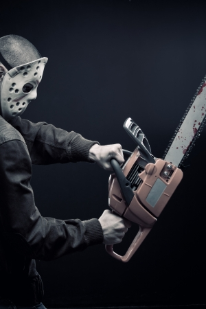 Guy with bloody chainsaw posing over dark background photo
