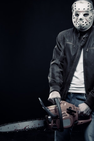Guy with chainsaw in mask posing over dark background