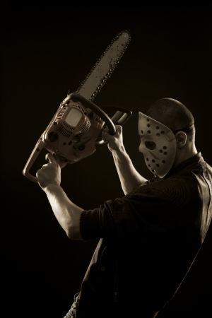 Maniac in mask with chainsaw posing over dark background photo