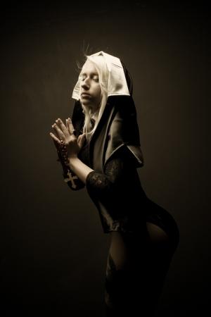 Pretty sexy nun posing over dark background