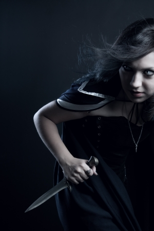 stealer: Girl with dagger posing over dark background Stock Photo