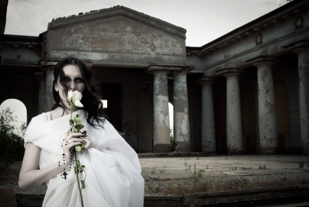 Pretty gothic girl with a  flower posing on a cemetery photo