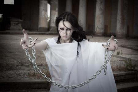 Pretty gothic girl with arms in chains photo