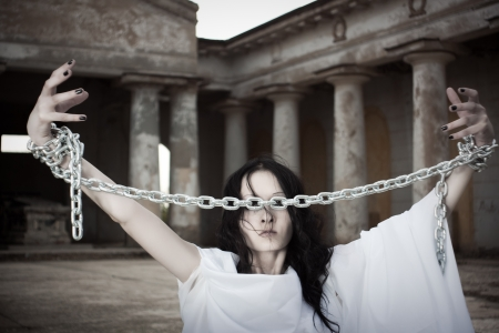 Pretty girl with arms in chains on a cemetery photo