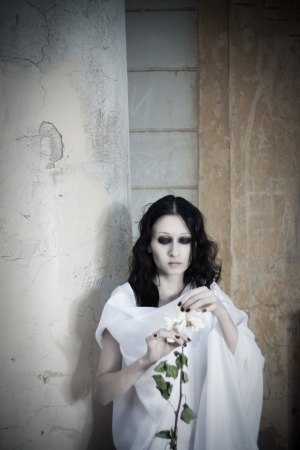 Pretty young gothic girl with flower photo