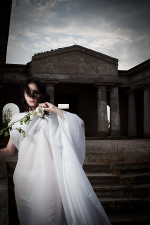 Pretty gothic girl in white clothes posing with rose photo