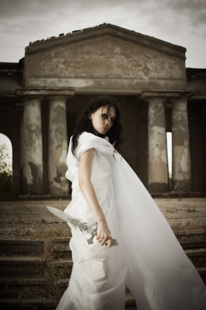 girl with knife: Pretty gothic girl posing with sword