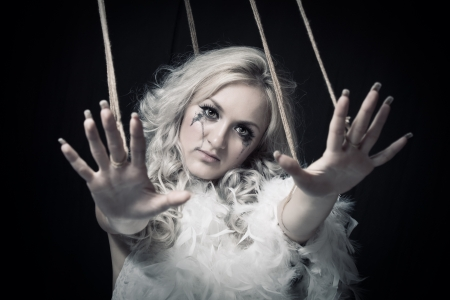 Pretty girl with ropes posing over dark background photo