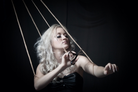 marioneta: Chica glamorosa con unas tijeras cortando las cuerdas sobre fondo oscuro
