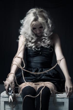 puppet woman: Chica linda g�tica con cuerdas que se sientan en el cuarto oscuro Foto de archivo