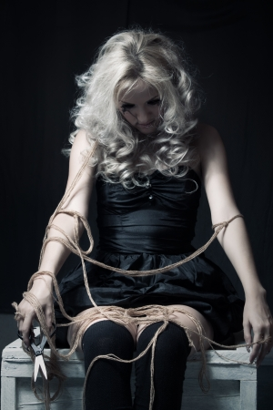 puppet theatre: Pretty gothic girl with ropes sitting in the dark room