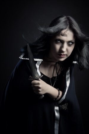 stealer: Pretty young girl with dagger posing over dark background
