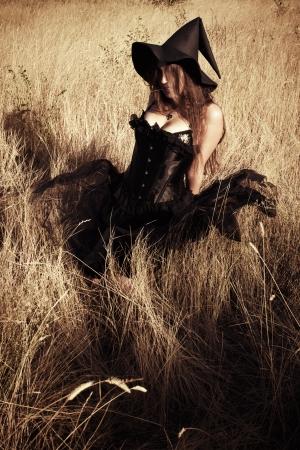 witchery: Pretty girl in black dress sitting in the field