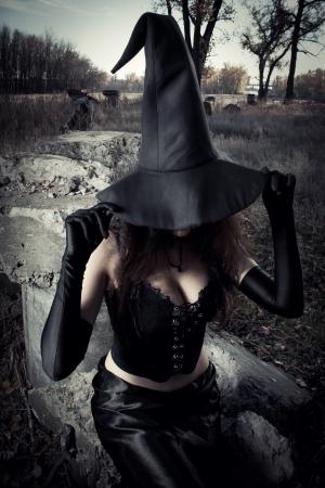 bruja sexy: Bruja con sombrero sentado en las piedras