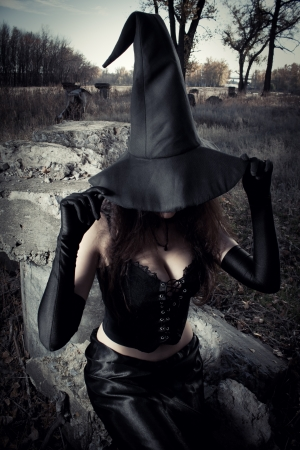 Witch with hat sitting on the stones