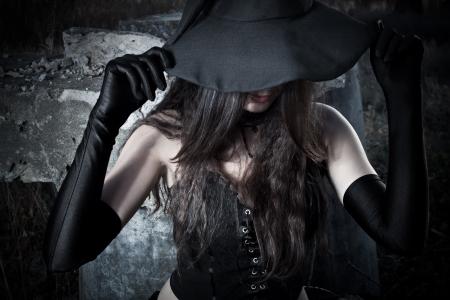 heks: Jonge heks houdt haar hoed Stockfoto