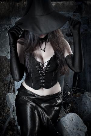bruja sexy: Muchacha bonita que sostiene el sombrero