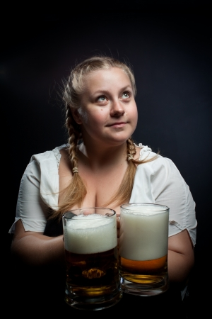 Pretty girl with beer posing over dark background photo