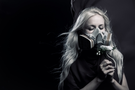 Pretty girl in gas mask holding flower in her hands photo