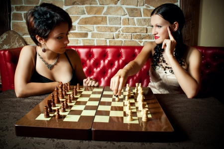Two pretty girl-friends friends playing chess photo