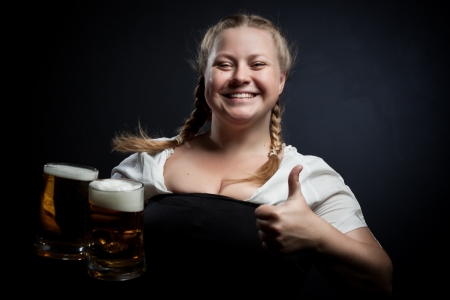 Cheerful Irish girl with beer over dark background photo