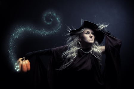 witch hat: Pretty witch holding pumpkin over dark background Stock Photo