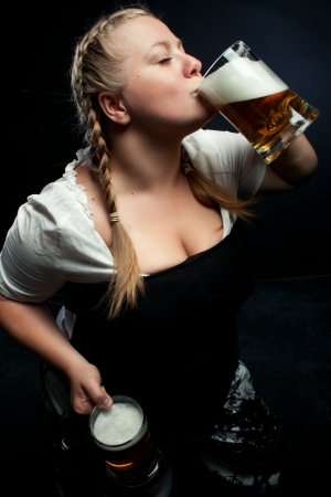 german girl: Irish girl drinking beer over darkbackground Stock Photo