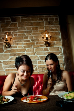 Two pretty girl-friends sitting at a restaurant photo