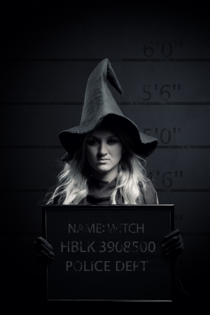 Mugshot of pretty witch in a police station photo