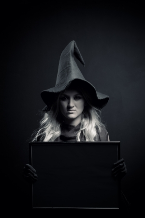 Pretty witch in hat holding empty banner over dark background photo
