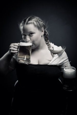 Pretty Irish girl drinking beer over dark background photo