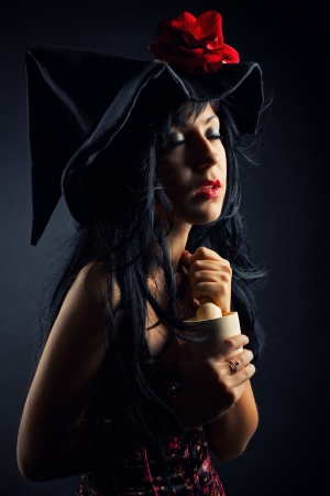 wizardry: Pretty witch in hat with mortar and pestle over dark background